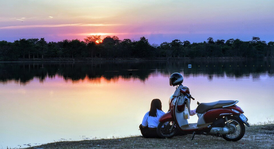 Woman by the lake with temporary moped insurance